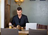 Young businessman having sandwich at restaurant