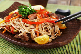 picture of noodles  - Chinese noodles with vegetables and roasted meat on plate on bamboo mat background - JPG