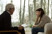 picture of psychologist  - Young attractive sad woman sitting at psychologist - JPG