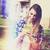foto of teenagers  - Closeup outdoors portrait of causal young millennial teenage girl smiling holding smart phone and texting - JPG