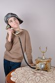 foto of newsboy  - Cute thoughtful young boy with tartan newsboy cap talking on the retro telephone - JPG