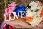 stock photo of romantic love  - Word Love and wedding bouquet of flowers on a romantic floral swing as a Valentine - JPG