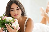 stock photo of peignoir  - Beautiful bride in white lingerie holding nuptial bouquet - JPG