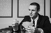 pic of poker hand  - Poker player in the casino with glass of whiskey and cards at the gaming table - JPG