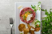 picture of sprinkling  - Beef tartar and homemade potato chips sprinkled with parmesan shavings and microgreens - JPG