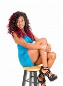 foto of short legs  - A young African American woman in a short blue dress sitting on a chair
