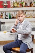 stock photo of over counter  - Anticipating a meeting. Young man in shirt and jacket talking over the phone and looking at his watch while sitting at the counter of the bar