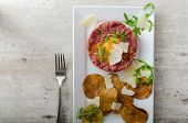 stock photo of tartar  - Beef tartar and homemade potato chips sprinkled with parmesan shavings and microgreens - JPG