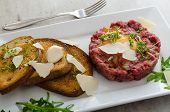 stock photo of tartar  - Beef tartar and toast bread with garlic sprinkled with parmesan shavings and microgreens - JPG