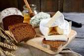 image of brie cheese  - Brie cheese rye bread slices roquefort and honey on a cutting board - JPG