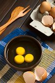 foto of egg whites  - Three raw eggs in rustic bowl with egg box with eggs and eggshells in the back photographed on dark wood with natural light  - JPG