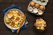 pic of scrambled eggs  - Overhead shot of scrambled eggs made with chorizo slices and onion on plate with toasted baguette slices and a wooden fork an egg box with eggs and eggshells on the side photographed on dark wood with natural light - JPG