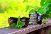 foto of peppermint  - Teapot with small cups and peppermint leaves - JPG