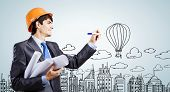 foto of engineering construction  - Young man engineer drawing sketches of construction project - JPG