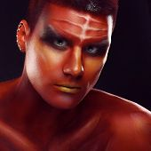 picture of adonis  - Portrait of a handsome young man in a red body painting - JPG
