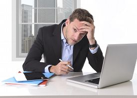image of suffering  - young attractive European businessman working in stress at office desk computer laptop suffering headache worried and frustrated isolated on white background - JPG