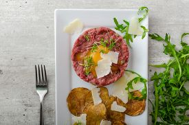 picture of tartar  - Beef tartar and homemade potato chips sprinkled with parmesan shavings and microgreens - JPG