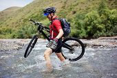 Biker Goes Over The Mountain River Ford