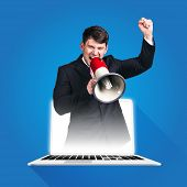 foto of shout  - Businessman in laptop Shouting Through Megaphone on blue background - JPG