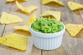 stock photo of nachos  - Cup with chunky guacamole served with nachos - JPG