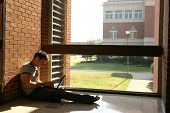 picture of school building  - college student in hallway by window working on laptop - JPG
