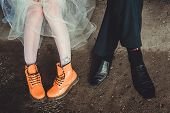 picture of woman boots  - Legs of a man and a woman in orange and black boots - JPG