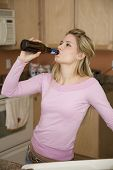 stock photo of underage  - Model Release 376 Young woman relaxing in the kitchen drinking a beer Underage drinking - JPG