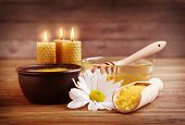 Spa concept. Composition of honey, sea salt and natural wax candles on wooden background poster
