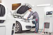 Full length of male engineer examining car in automobile repair shop poster