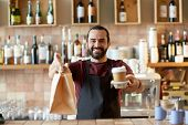 small business, people, takeaway and service concept - happy man or waiter in apron holding coffee c poster