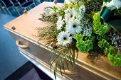stock photo of funeral  - A coffin with a flower arrangement at a mortuary - JPG