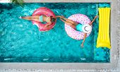 Two people (mom and child) relaxing on donut lilo in the pool at private villa. Inflatable ring and  poster