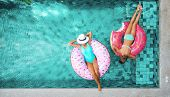 Two people (mom and child) relaxing on donut lilo in the pool at private villa. Summer holiday idyll poster