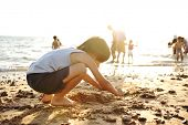 pic of hand-barrow  - Kid on beach in sand playing - JPG