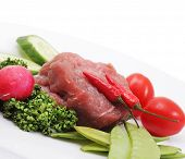 Vegetables and raw meat on a plate. Isolated on a white background