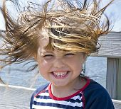 Windy hair, a girl on the beach when it blows hard