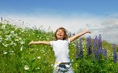 image of beautiful flower  - Little girl standing on a meadow in a field of beautiful flower and has fun - JPG