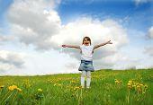 Little girl standing on a meadow in a field of beautiful flower