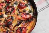White fish fillet with tomatoes and lemons in baking dish