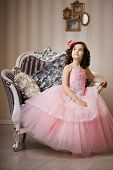A beautiful girl, a child on a chair in a nice dress