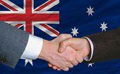 Apretón de manos de hombres de negocios después de mucho delante de la bandera de Australia