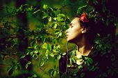 Woman Posing With Flower In Hair In Green Tree Leaves On Spring On Natural Background. Youth, Beauty poster