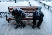 Two Unrecognizable Dirty Homeless Men Or Alcoholics Or Drug Addicts Are Sleeping On Bench In Cold Wi poster