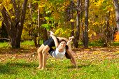 stock photo of dhanurasana  - Man and woman practice Yoga dhanurasana under urdhva dhanurasana pose in forest - JPG