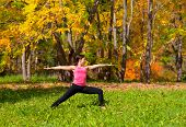 pic of virabhadrasana  - Woman exercises in the autumn forest yoga virabhadrasana pose - JPG