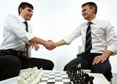 Two men handshaking with chess figures on chess board near by