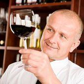 At the bar - senior barman hold glass red wine degustation