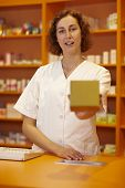 Female pharmacist behind counter explaining usage of medicine