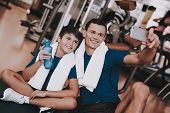 Young Father And Son Sitting On Mats In Sport Club. Healthy Lifestyle Concept. Sport And Training Co poster