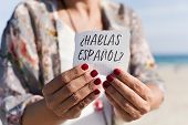 closeup of a caucasian woman outdoors showing a piece of paper with the question hablas espanol, do  poster